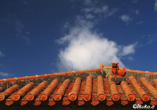 赤瓦屋根の上のシーサーと雲