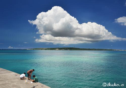 夏雲と釣りをする子供たち
