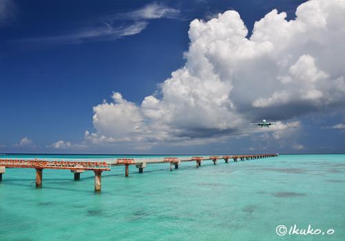 青い海の中を近づく飛行機