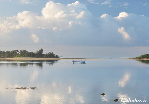 鏡のような海を走る漁船