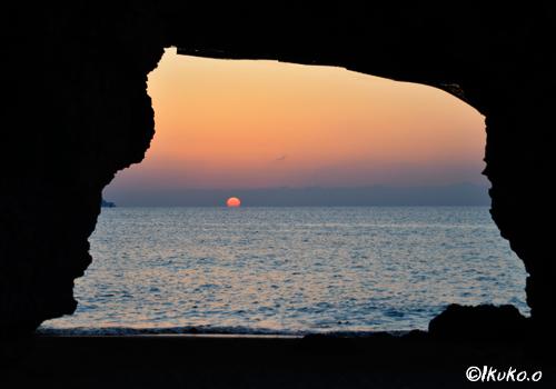 風洞の先の水平線に沈む太陽