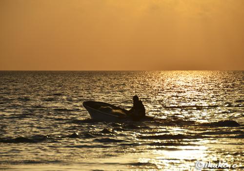 夕暮れの海に漕ぎ出す漁船