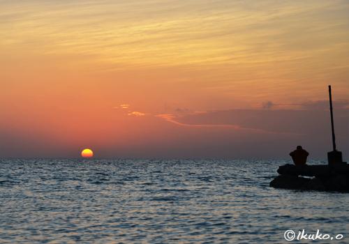 球体の夕日と釣り人