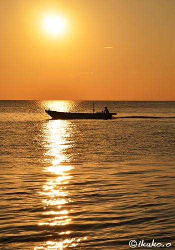 輝く光の帯を横切る漁船