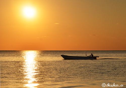 夕暮れの海と港に帰る漁船
