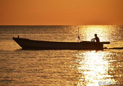 夕陽と海人のシルエット