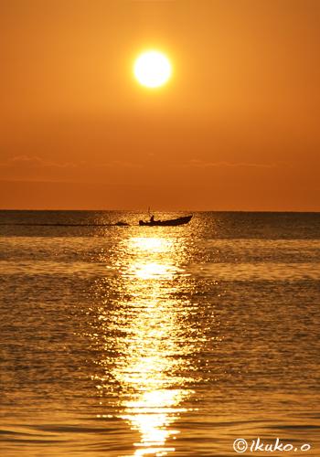 夕陽に輝く海と漁船